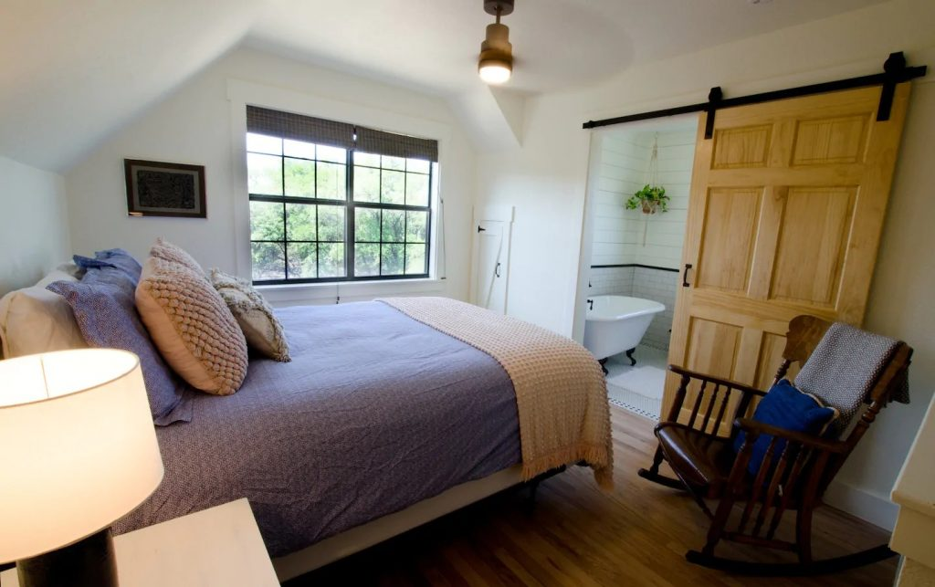 A beautiful master bedroom and bathroom, with natural lighting, a gorgeous sliding barn door, and a claw foot tub.  Lovely cabin getaway in Texas!