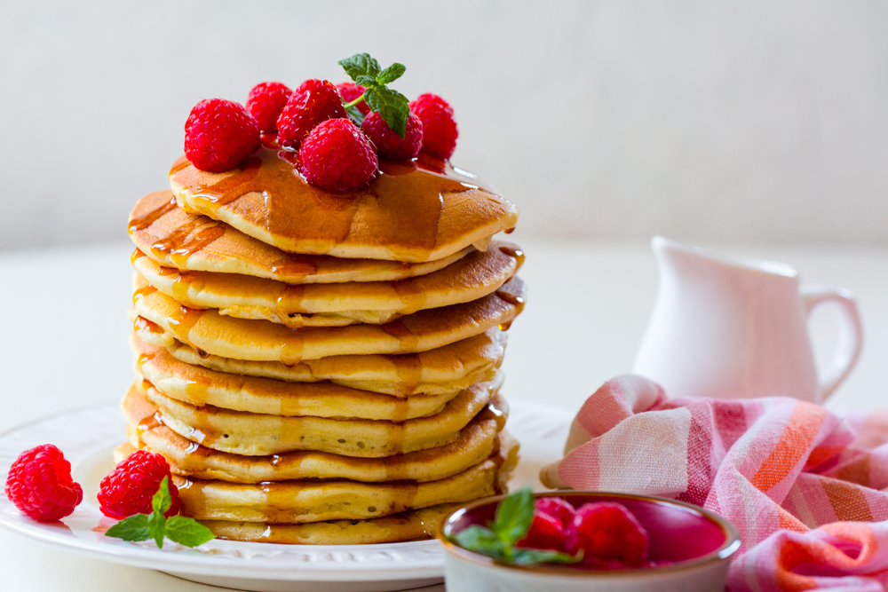 A tall stack of pancakes with raspberries. Get your fill of pancakes at one of the best restaurants in San Antonio: Snooze an A.M. Eatery