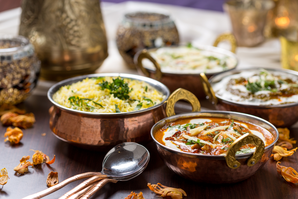 Four copper bowls filled with delicious Indian food. Find this at Tarka Indian Kitchen