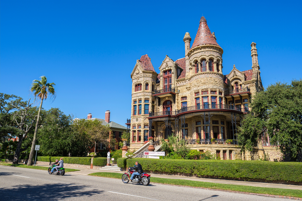 Bishop's Palace on a sunny day with people riding motorcycles in front on their texas road trip