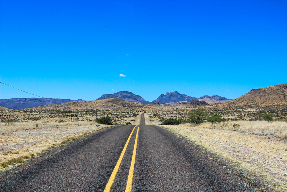 long empty paved road surrounded by desert landscape on a sunny day