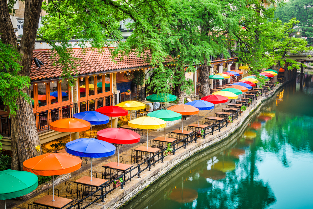 Photo of colorful umbrellas on a  restaurant patio lining the river walk in San Antonio, one of the best weekend getaways in Texas.