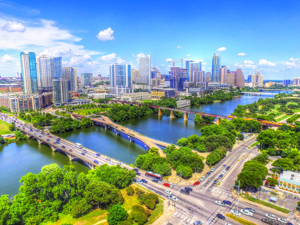 An aerial view of the Austin skyline. There are bridges going over a large river and you can see cars on them. There are lots of tall buildings, green space and trees near the river, and the sky is very blue.