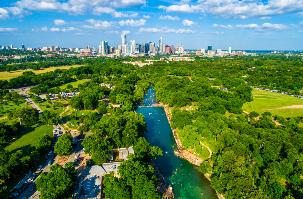An aerial view of a large long pool that is fed by a natural spring. The pool is a long rectangle that is in a grassy park. There are trees surrounding the pool. The water is a beautiful blue and you can see people swimming in it. In the distance you can see the Austin skyline. One of the best Texas day trips.