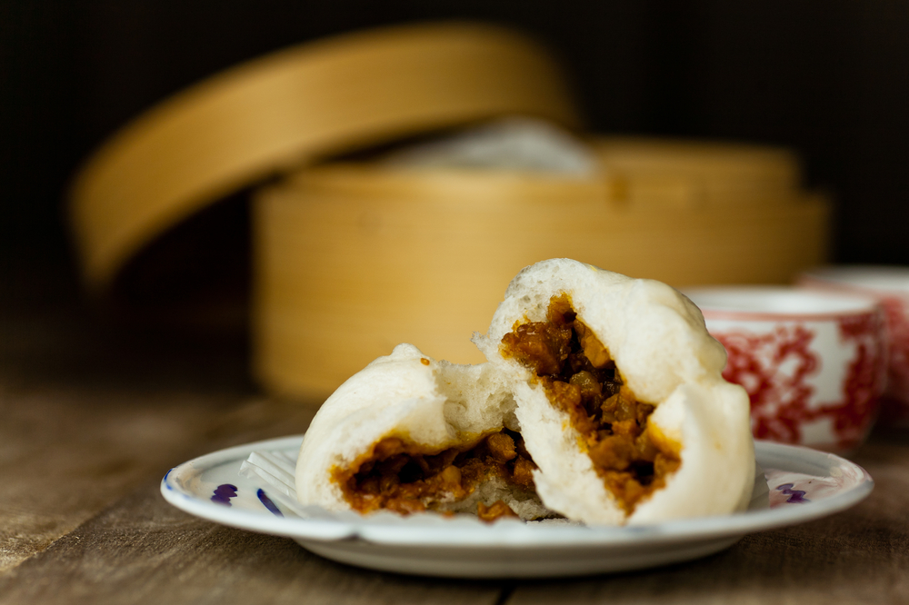 A small plate with two Asian steamed bbq pork rolls. you can see the inside of the rolls where there is meaty filling. In the background you can see an Asian steaming basket and two red and white ceramic cups.