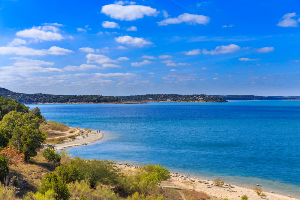 Looking out at the shoreline of the Canyon Lake. It is a large reservoir lake that has sandy shores with trees and grasses on the shore. The water is bright blue and so is the sky. It is one of the best Texas day trips.