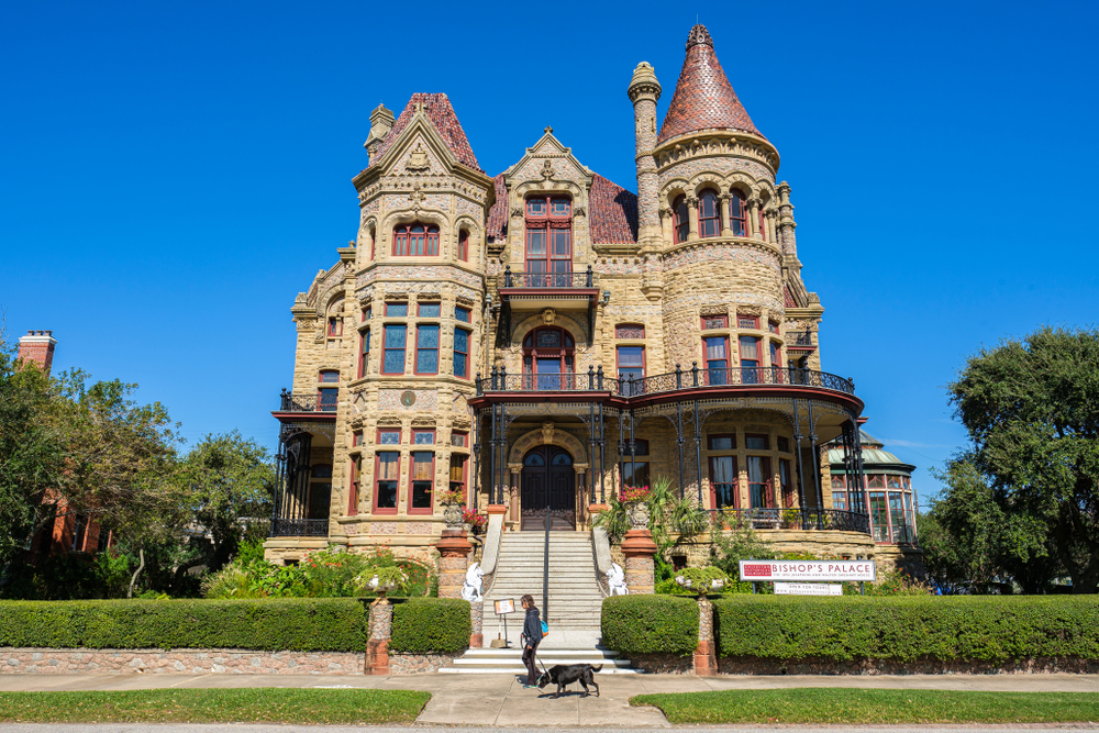 Woman walking dog in front of Bishop's Palace in Galveston, TX. A castle in Texas