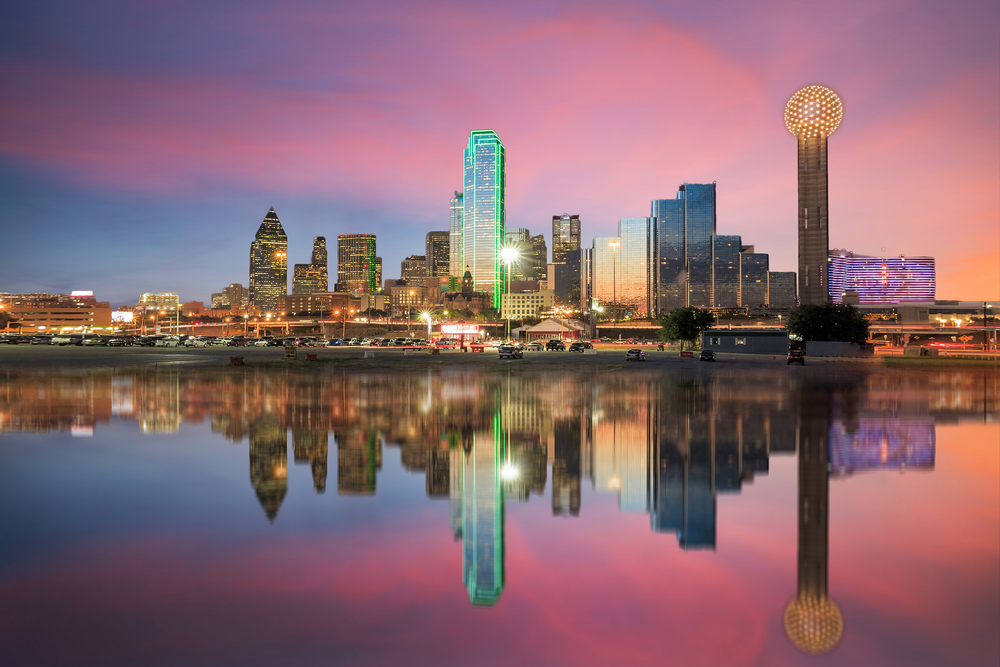 The Dallas skyline at twilight from the view of the river. The skyline is all lit up and the sky is mostly pink and purple with some blue. The sky and the skyline is reflected in the river.