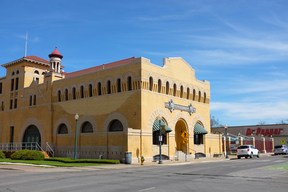 The exterior of a 20th century building. It is a creamy color and has arched windows all along the top. There is an arched doorway and behind it you can see a building that says 'Dr. Pepper'. It is one of the best day trips from Dallas.