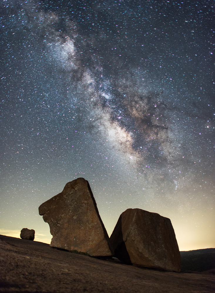 An image of two large uniquely shaped rocks with the Milky Way in the sky behind them. The rocks are somewhat in shadow.
