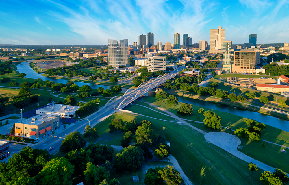 An aerial view of Forth Worth, a city just outside of Dallas. There is a river running through the city, a bridge with arches on it, and a typical city skyline. Near the river there are a lot of grassy areas and trees. It is a sunny day.