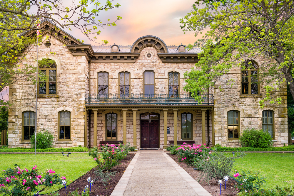 An old stone building that is architecturally influenced by antique German building. In front of it is a walkway that has flower beds with pink flowers on either side and then a grassy lawn. You can also see a few trees.