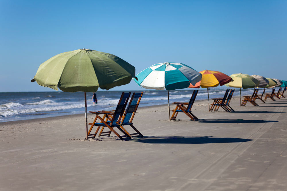 A group of beach chairs and different colored umbrellas all lined up. They are sitting on the sandy shore of Galveston Beach, one of the best Texas day trips. The chairs are facing the ocean and you can see waves crashing and someone standing in the water.
