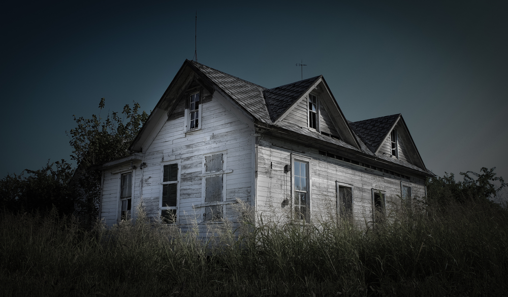 A scary old white abandoned house with broken windows and high uncut grass one of the most haunted places in texas