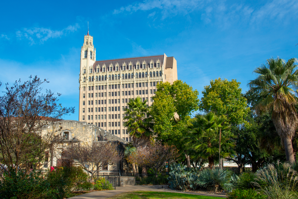 A tall old styled building named The emily morgan hotel with trees in the foreground on a sunny day one of the most haunted places in texas