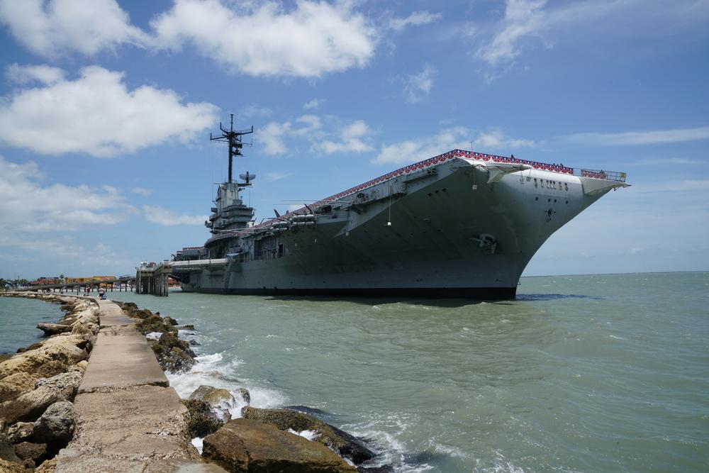 A large ship named The USS Lexington docked on a sunny day
