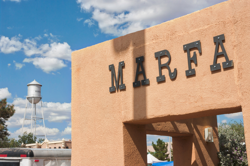 Marfa sign on pink wall with water tower in the background