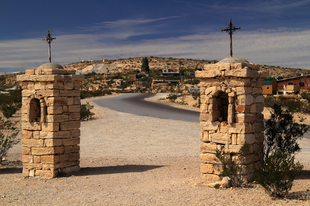 Two stone pillars with crosses on top at the entrance to Terlingua Ghost Town