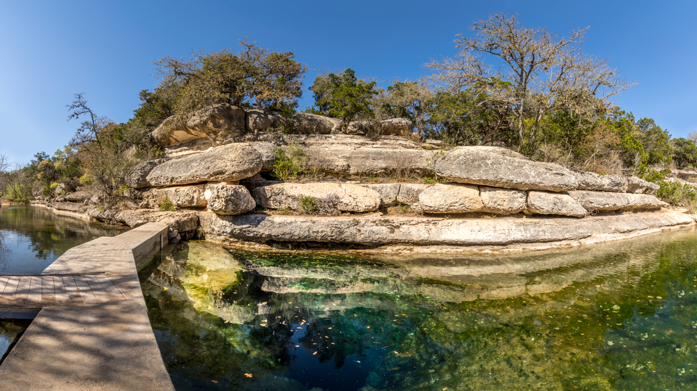 Rocks around a deep pool with trees on top of the rock.