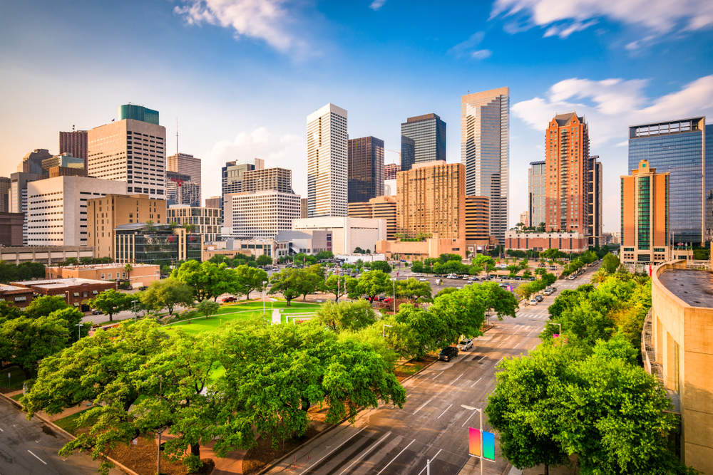 The skyline of Houston Texas. There are lots of skyscrapers. You can also see a large park with trees all around it and a large green space in the middle. It is a sunny day with a few clouds in the sky. One of the best day trips from Dallas.