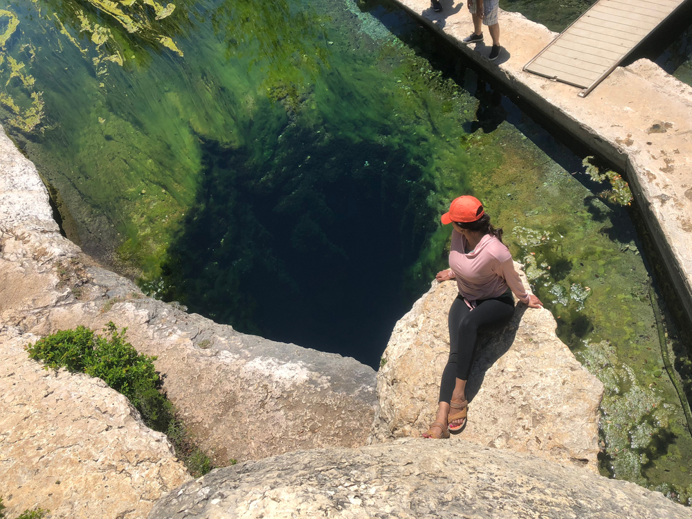 A woman wearing black leggings, a blush colored shirt, and a red hat sitting on a rock. The rock is hanging over one of the underwater caves in Jacobs Well. The cave is a large hole that descends into total darkness. The water is crystal clear and the rocks have green moss growing on them.