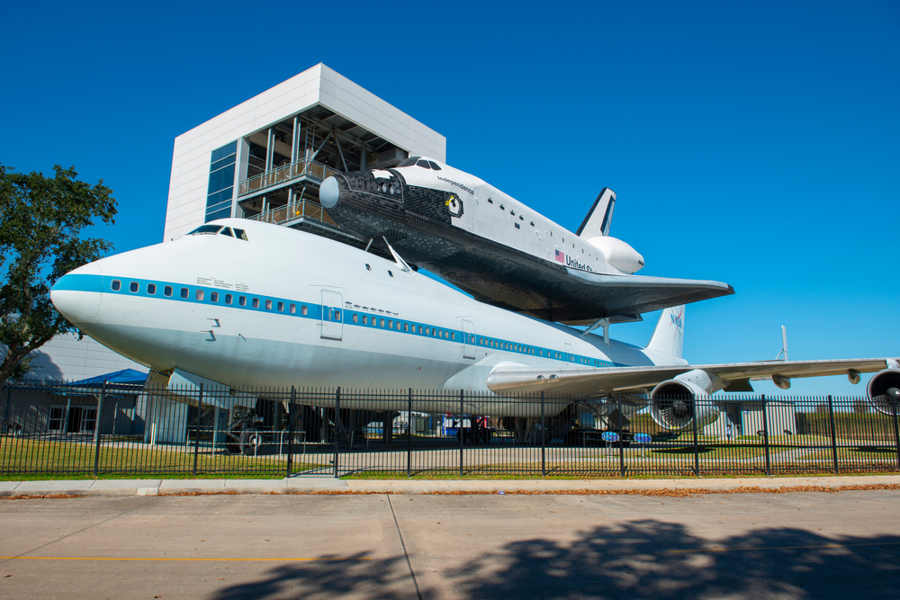 A NASA space shuttle perched on a large airplane. There is a black fence surrounding it and behind it you can see a square building with decks on it. It is one of the best Texas day trips.