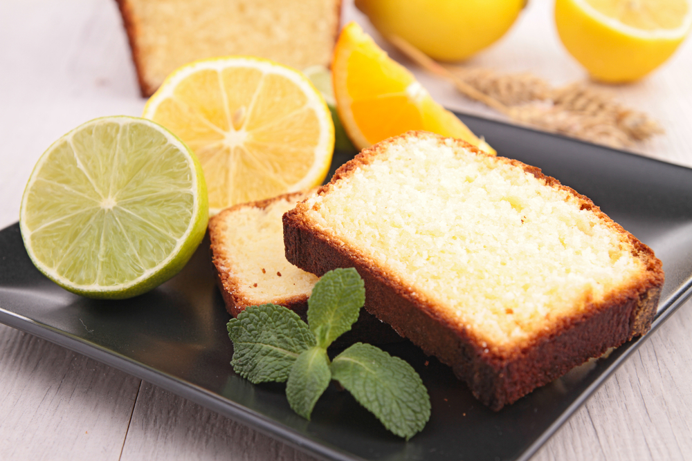 Two slices of lemon pound cake on a black ceramic plate. On the plate there are also slices of lemon, lime, and orange. There is also a sprig of fresh mint.