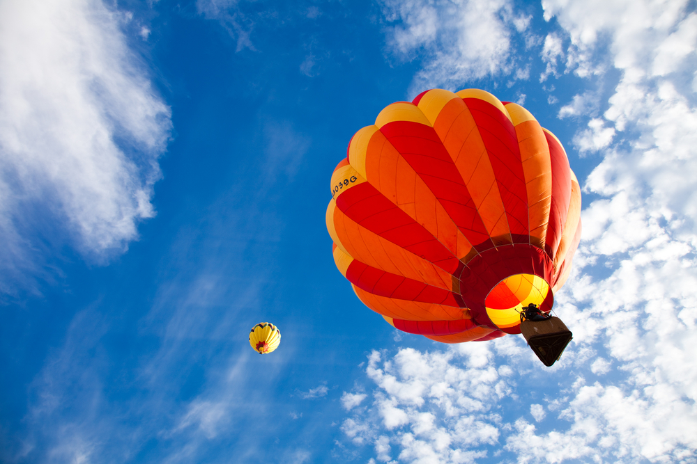 Looking up at two hot air balloons in the sky. The sky is very blue with some scattered clouds. The balloons are chevron patterned in yellow, orange, and red.