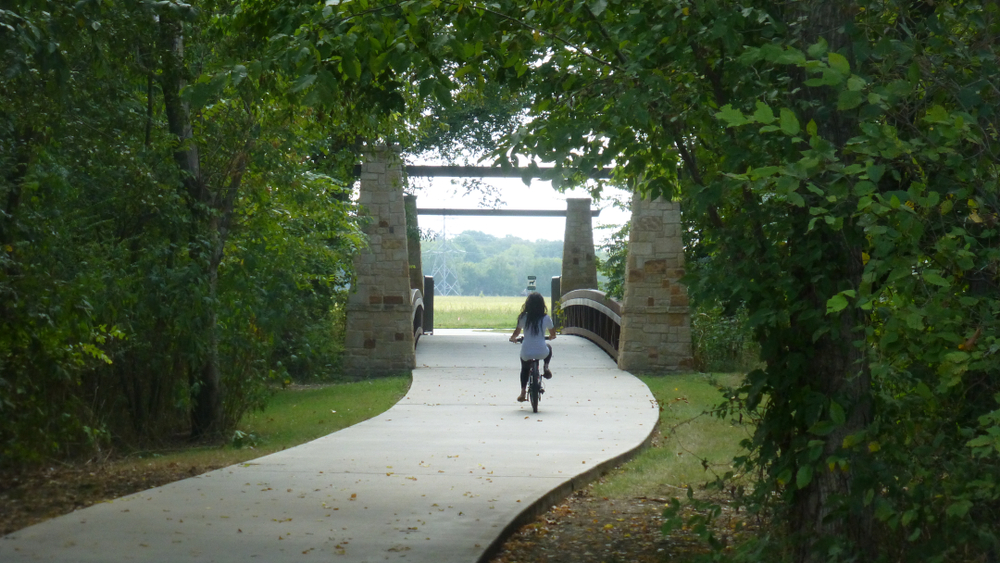 A woman with long hair riding a bike on a pathed trail. The trail is surrounded by green trees and grass. In the distance there is a bridge and you can see a field with trees in it. It is one of the best day trips from Dallas.