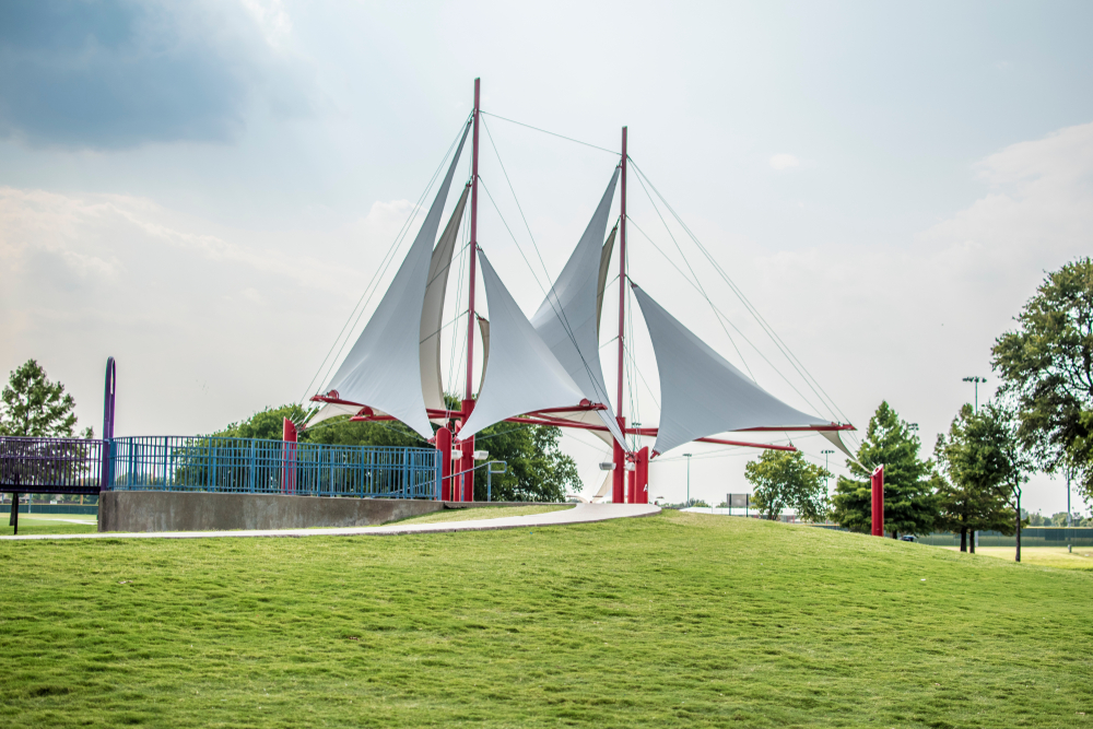 A sailboat sculpture that is just the sails. The sails are white and there are red metal bars connecting the sails. The sculpture is on a grassy lawn and has a sidewalk leading up to it. There some trees nearby.