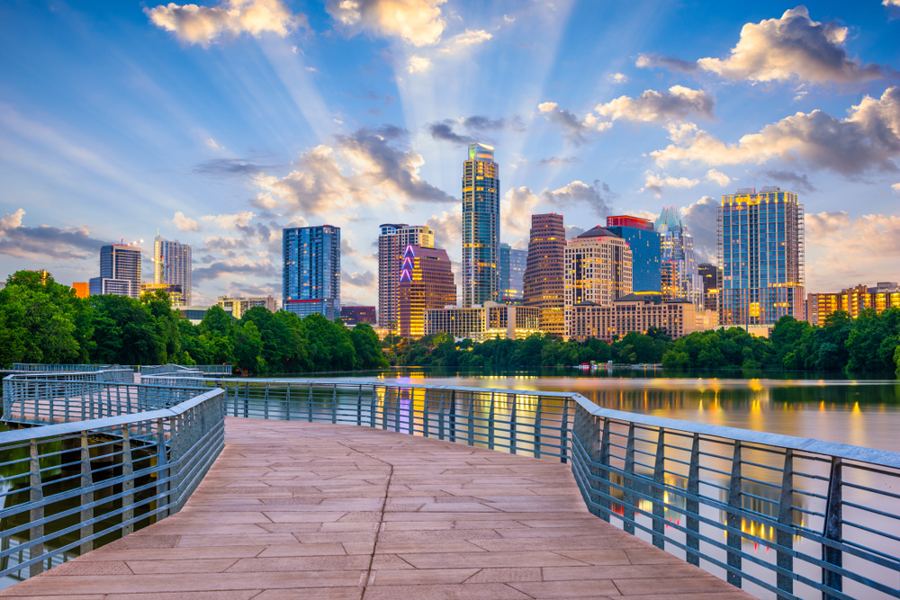 Looking at the Austin city skyline from a paved walkway that crosses over the river. It is twilight so the sun is starting to set and the buildings are all lit up. You can see lights reflecting in the river.