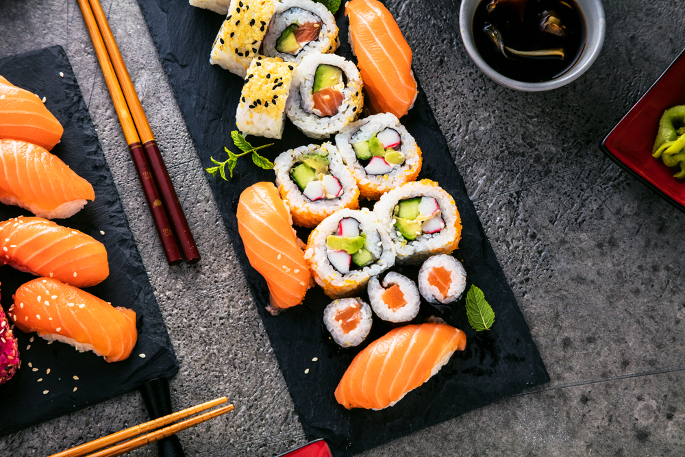 A black stone slab and part of a black stone slab covered in different sushi and sashimi rolls. You can see chopsticks, a small bowl of soy sauce, and the grey stone table. Its one of the best sushi restaurants in Austin.