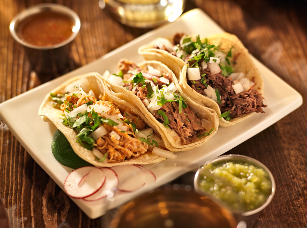 A plate with three different types of tacos on it. They are shredded chicken, shredded pork, and shredded beef. They have fresh cut cilantro and onion sprinkled on top. There is a lime wedge on the plate and dishes of different salsas on the wood table around the plate. A great meal to be found at restaurants in Austin.