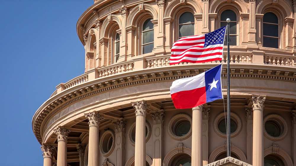 An ornate state building in Texas. It is made of a tan colored stone and has lots of intricate carvings and details. In front of it there is an American and Texas flag flying on a flag pole.