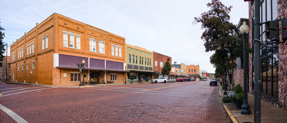 View of downtown Nacogdoches, brick streets and historic store fronts on a main street.