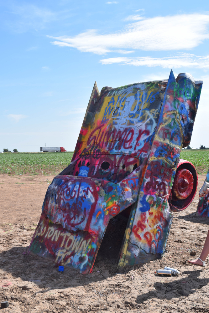 photo of a Cadillac sticking out of the ground covered in spray painting