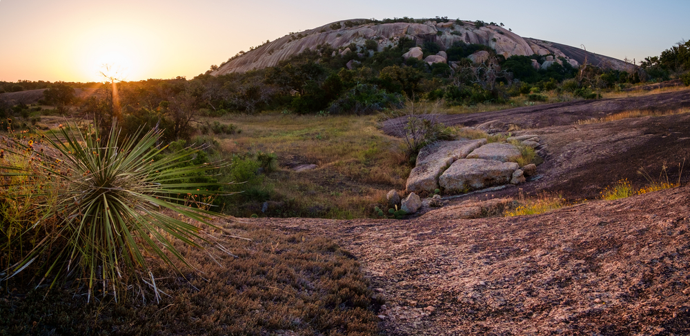 a large rock hill at sunset surrounded by sparse greenery one of the best things to do in texas hill country