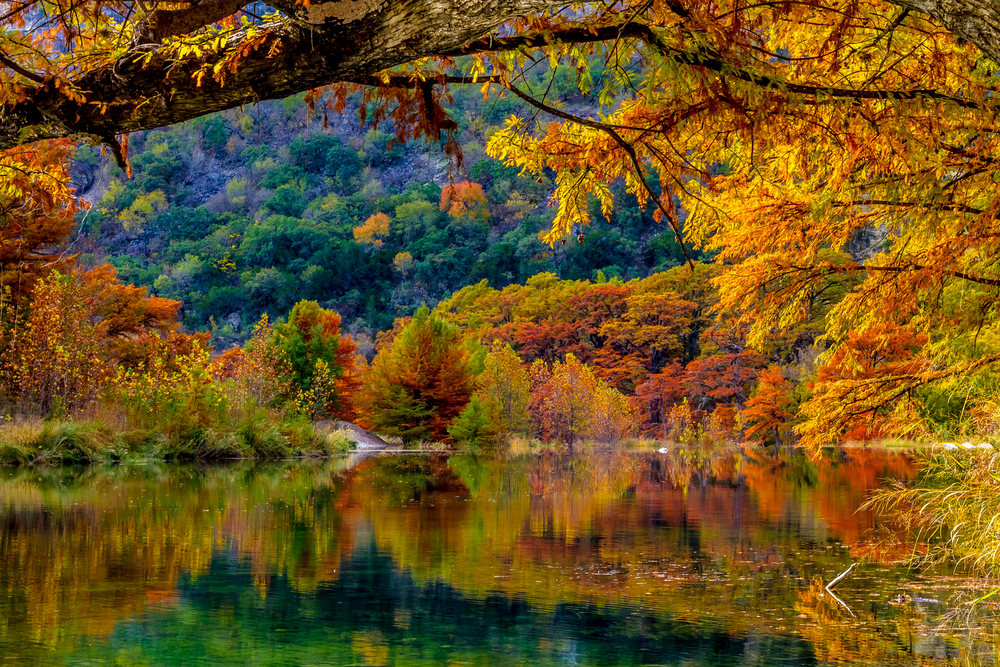trees during the fall with their leaves changing colors surrounding a lake, one of the prettiest things to do in Texas hill country