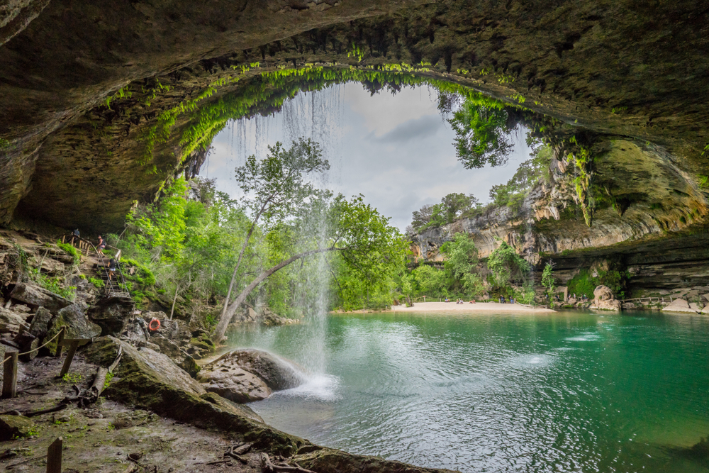 a pool of jade green water with a waterfall pouring into it one of the best things to do in texas hill country