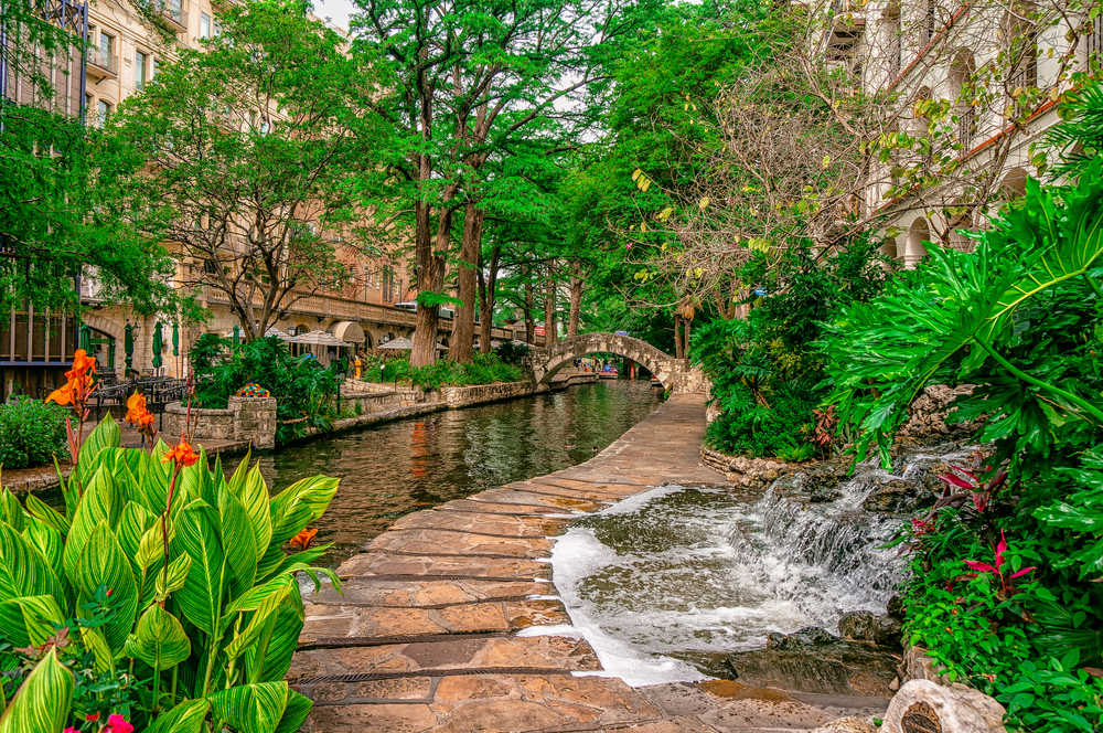 a beautiful downtown river with a stone pathway alongside. Lush greenery and stone building surround the area