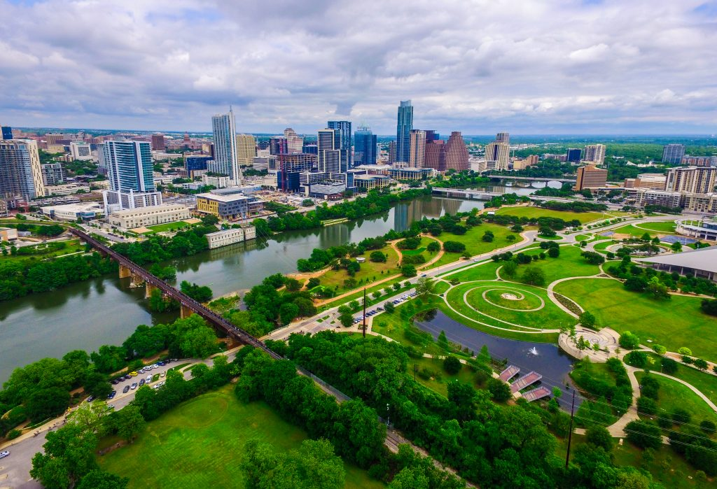 An aerial shot of downtown Austin, showcasing its bridges, gardens, and waterways.