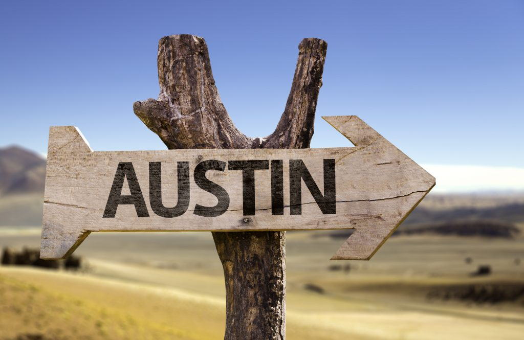 A sign on the side of the road indicates the way to Austin