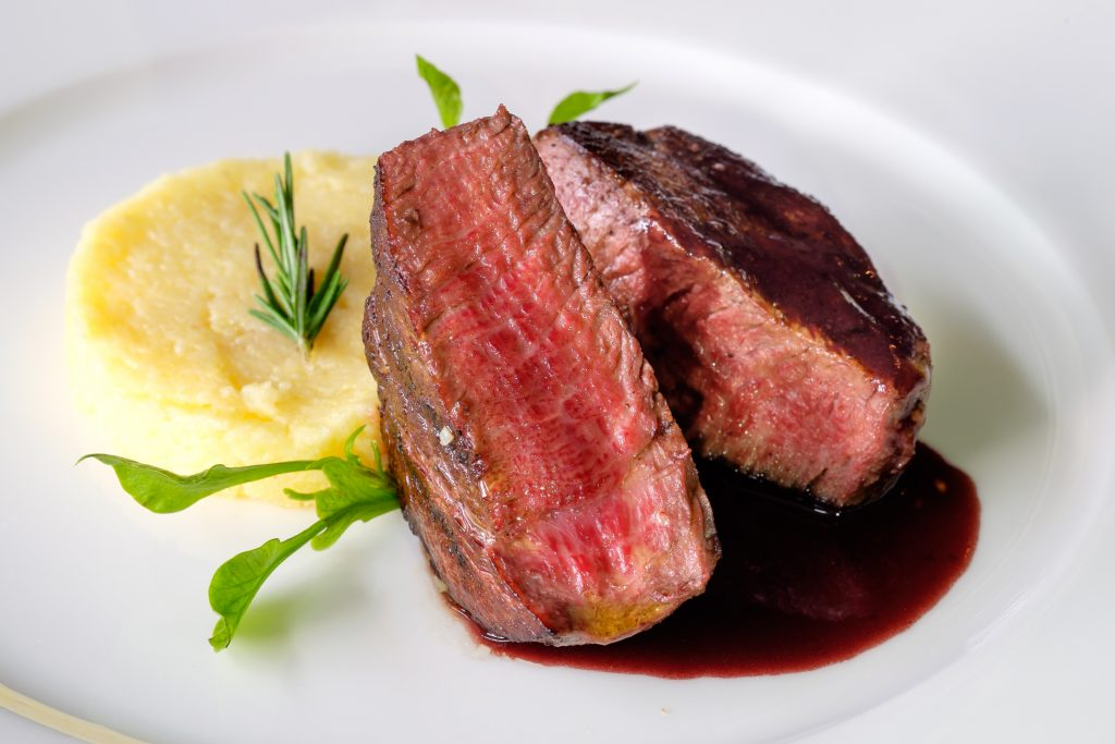 Wagyu Beef on white plate with mashed potatoes
