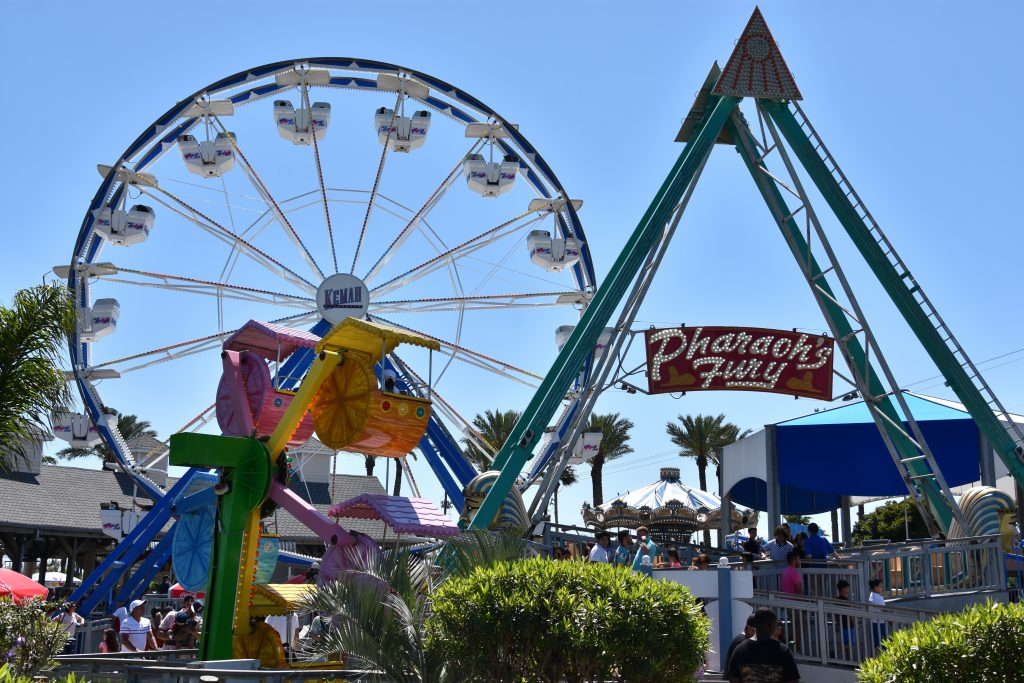 Farris Wheel at amusement parks in Texas surrounded by families on a sunny, blue day.