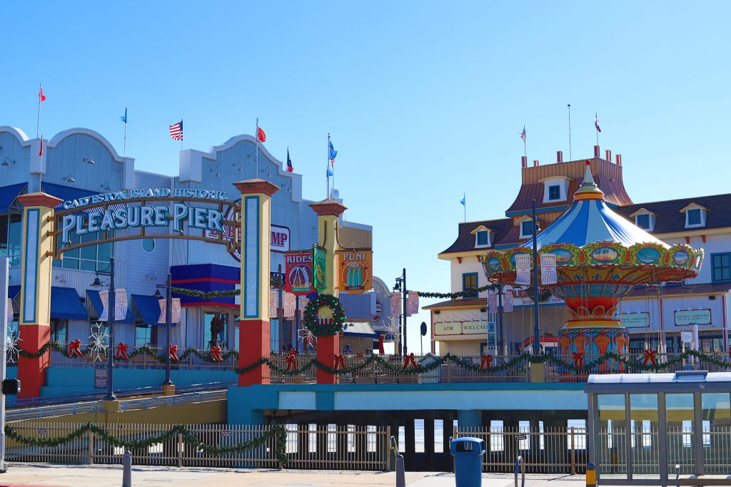 Amusement parks in Texas that are located on the Pleasure Pier with cartoonish buildings and bright colors.
