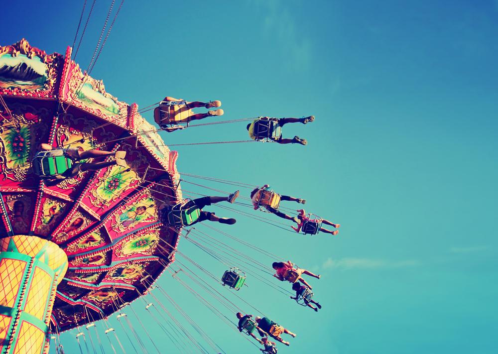 Fair-goers enjoy amusement parks in Texas, swinging against a blue sky.