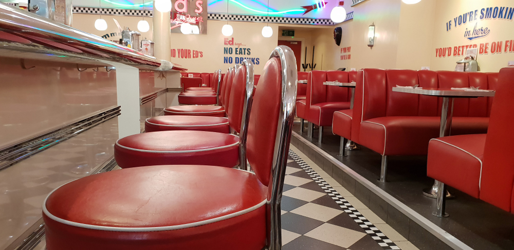 Red barstools at counter and red booths, black and white checkered floor, at a classic 1950s style diner with neon lights serving breakfast in dallas