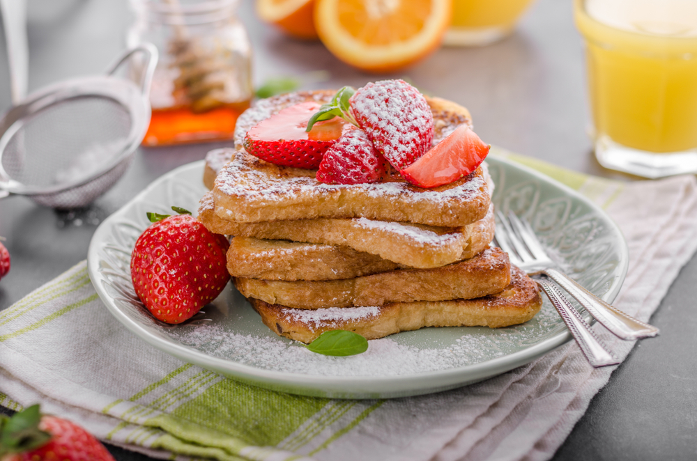 Stack of stuffed french toast on a plate sprinkled with powdered sugar with orange juice in the background served for breakfast in Dallas