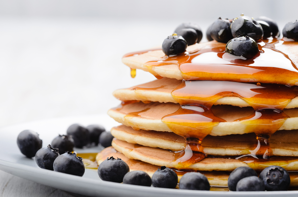 Blueberry pancakes covered in syrup at best breakfast restaurant in Dallas