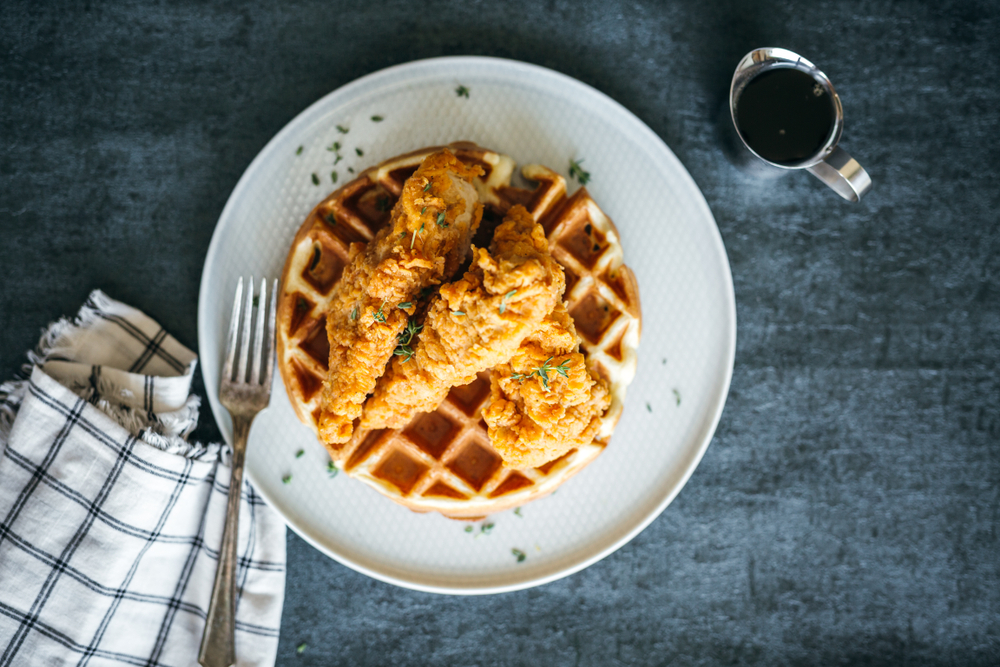 from above plate of chicken and waffles with a fork and blue striped napkin and syrup in metal dish, served for breakfast in Dallas